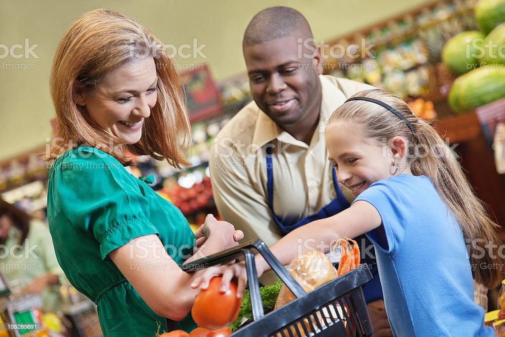 Little girl helping load vegetables with mom and produce worker royalty-free stock photo