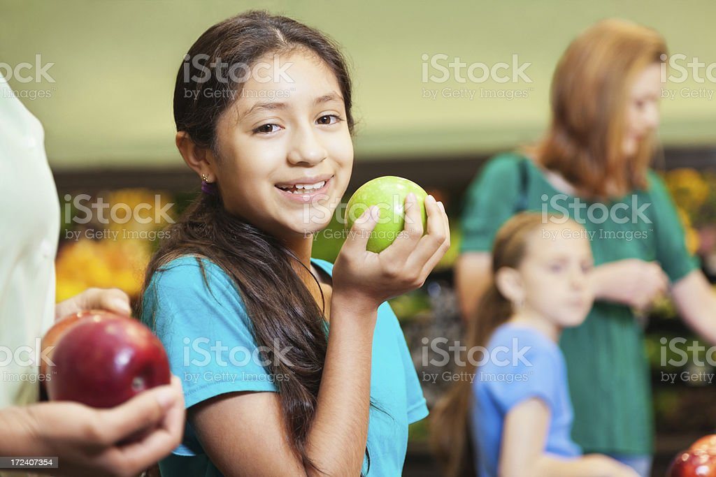Little girl helping mom shop for healthy food in supermarket royalty-free stock photo