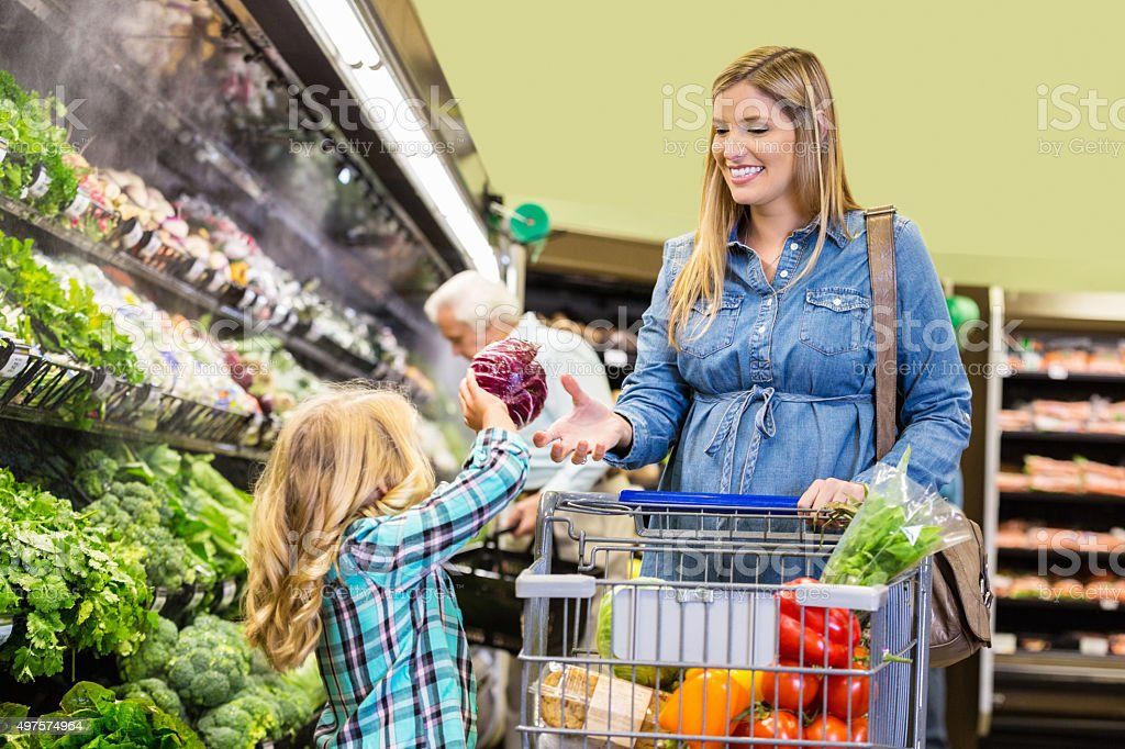 Little girl helping mom shop for vegetables in supermarket stock photo