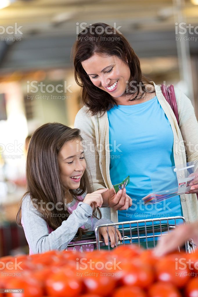 Little girl helping mother shop for groceries and use coupons stock photo