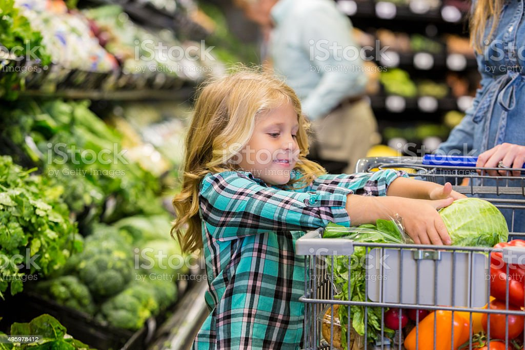 Little girl helping mother shop for produce in grocery store stock photo