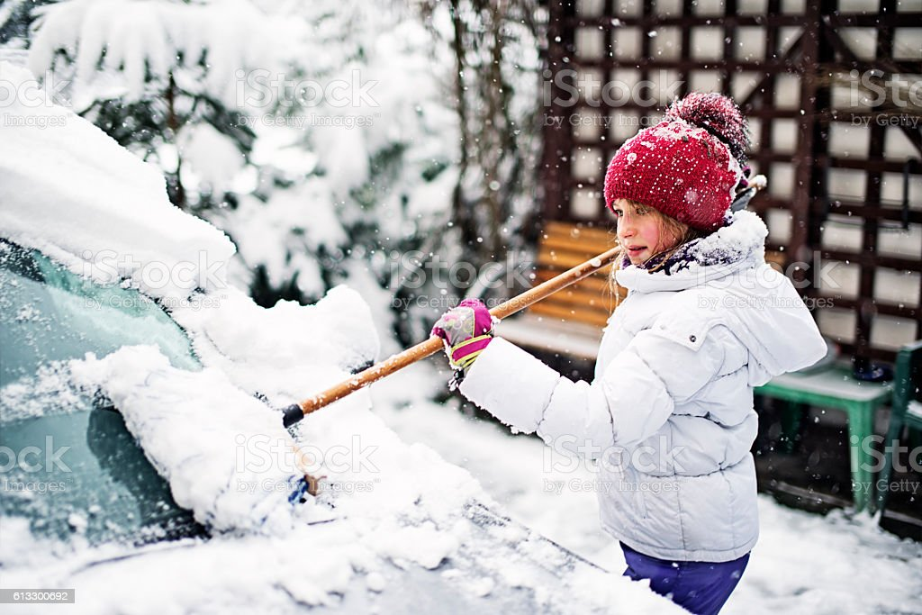 Little girl helping to clean family car after winter blizzard stock photo