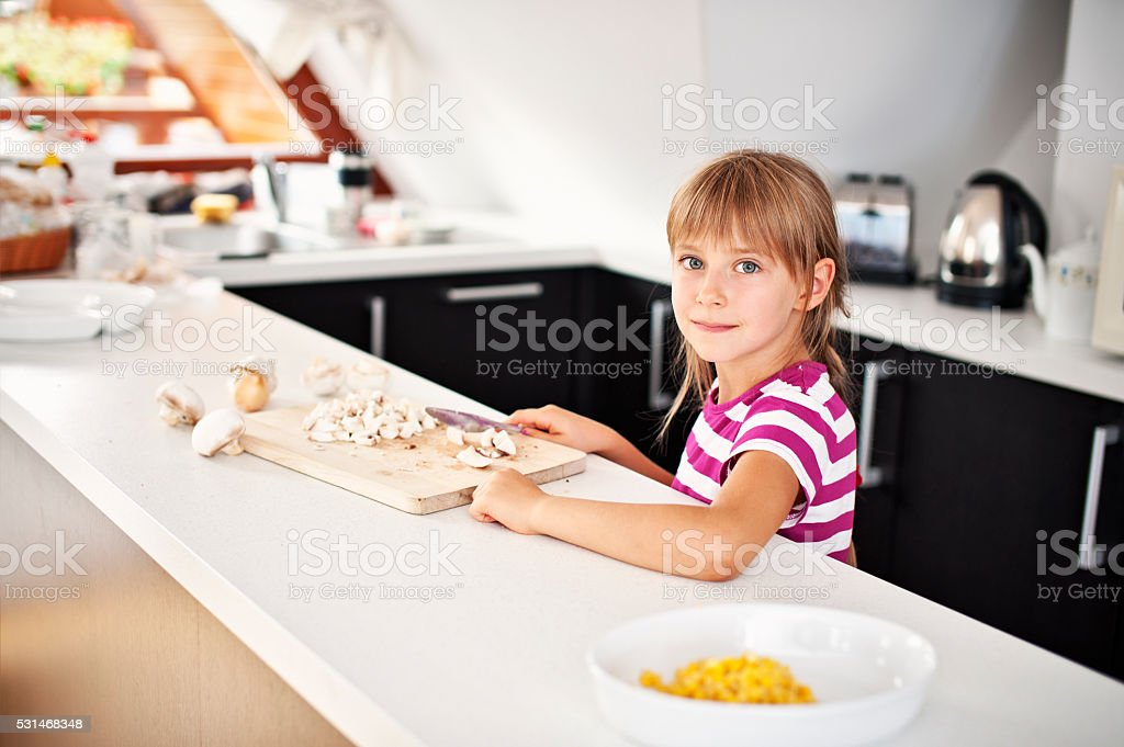 Little girl helping to prepare a meal stock photo