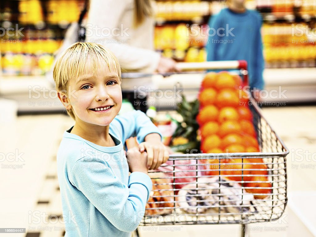 Little girl helps push trolley on supermarket shopping trip royalty-free stock photo