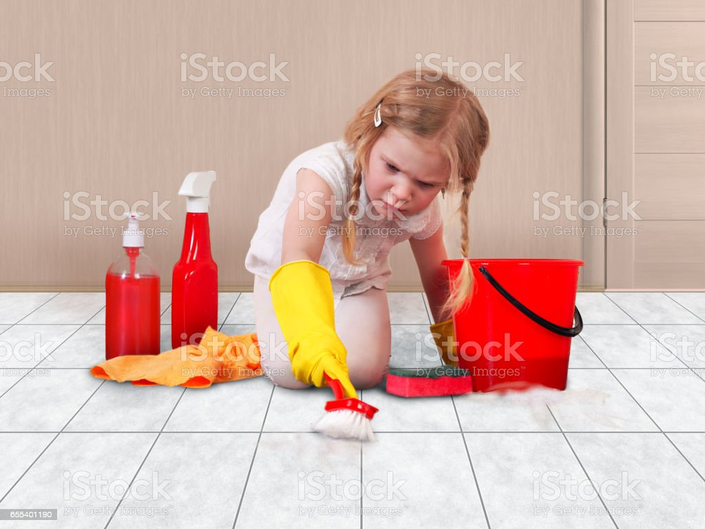 Little girl helps with the cleaning in the house. Child happily washing floors stock photo