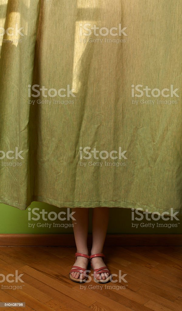 little girl hid behind the curtain stock photo