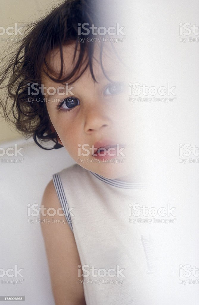 Little girl hidden behind curtain royalty-free stock photo