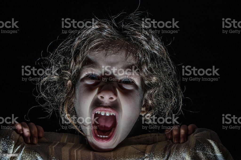 Little girl  hiding behind her bed sheets and screaming stock photo