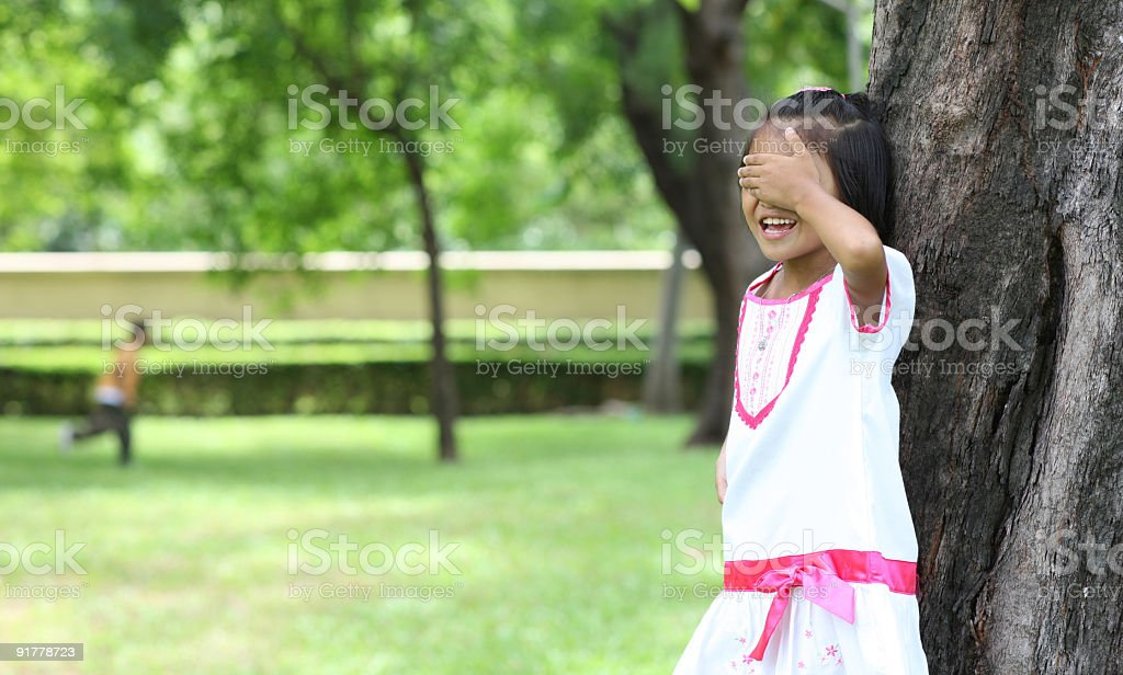 Little girl hiding eyes in hide and go seek stock photo