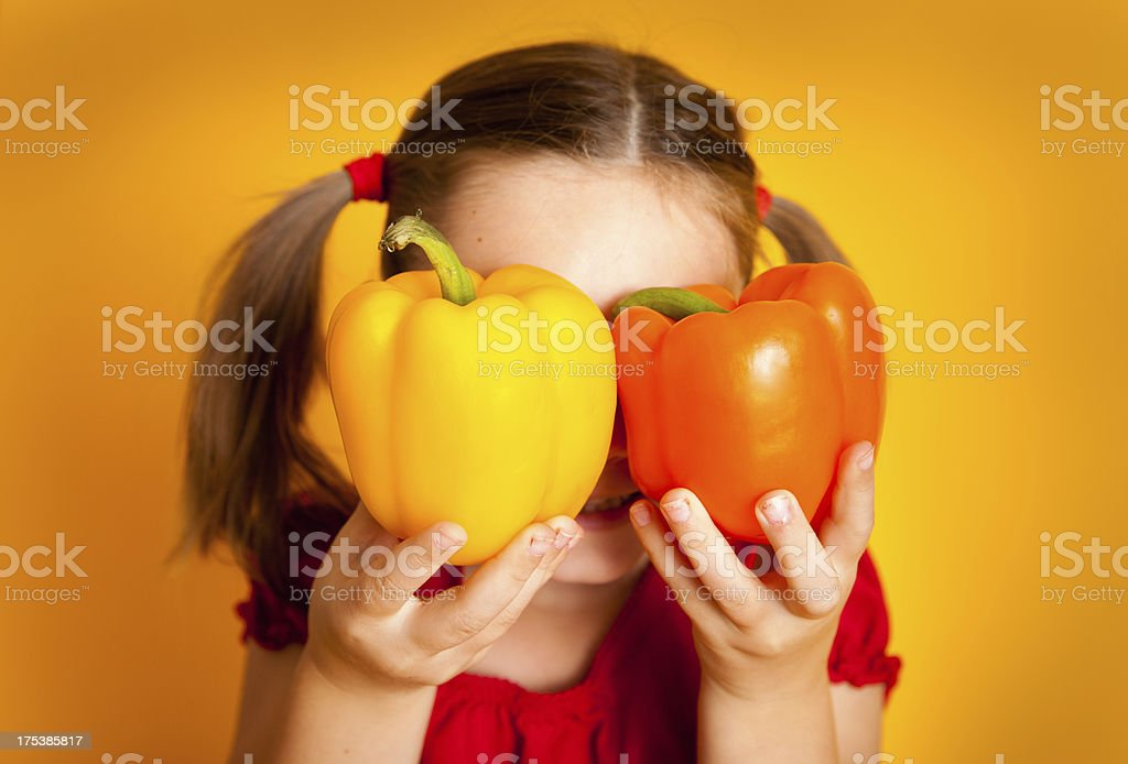 Little Girl Hiding Face Behind Yellow and Orange Peppers royalty-free stock photo