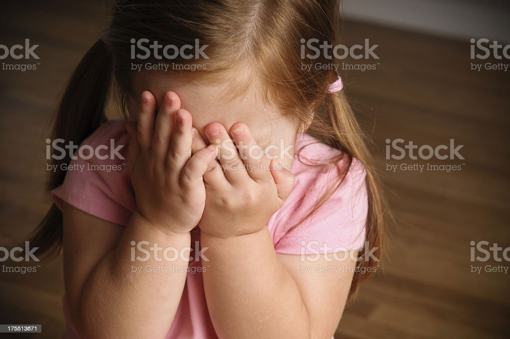 Little Girl Hiding Her Face From Camera stock photo