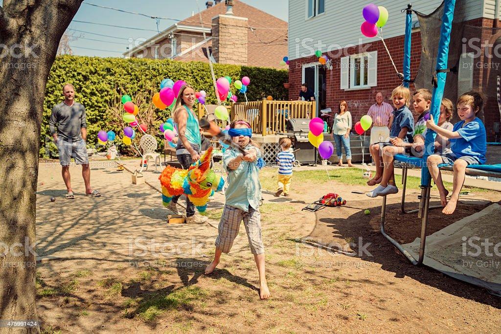 Little girl hitting pinata at birthday party in suburb backyard. stock photo