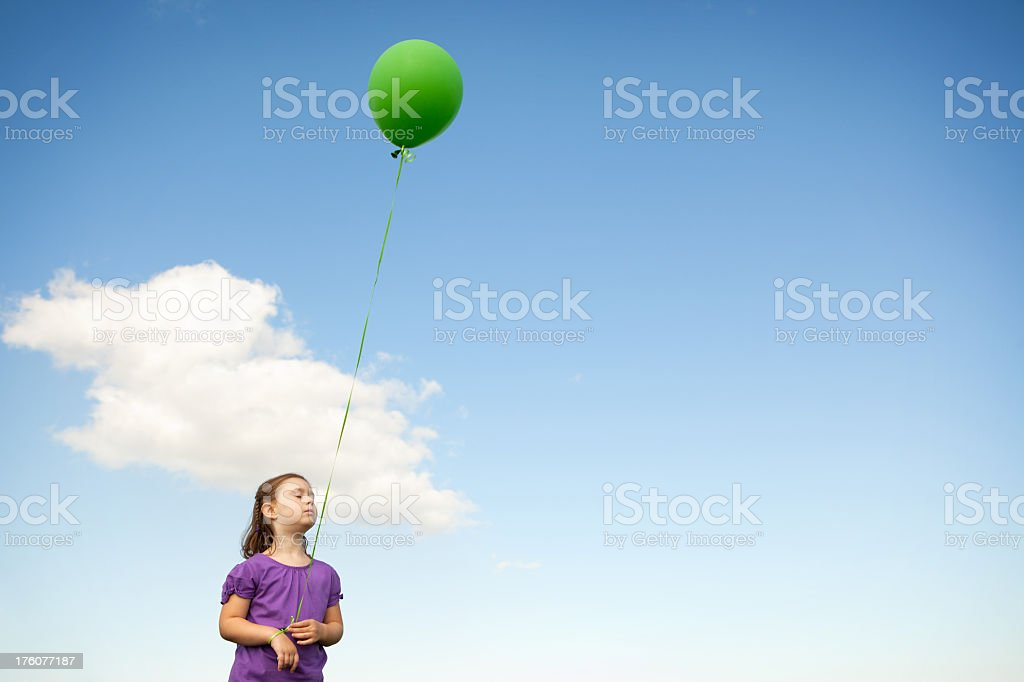 Little Girl Holding a Balloon and Day Dreaming royalty-free stock photo