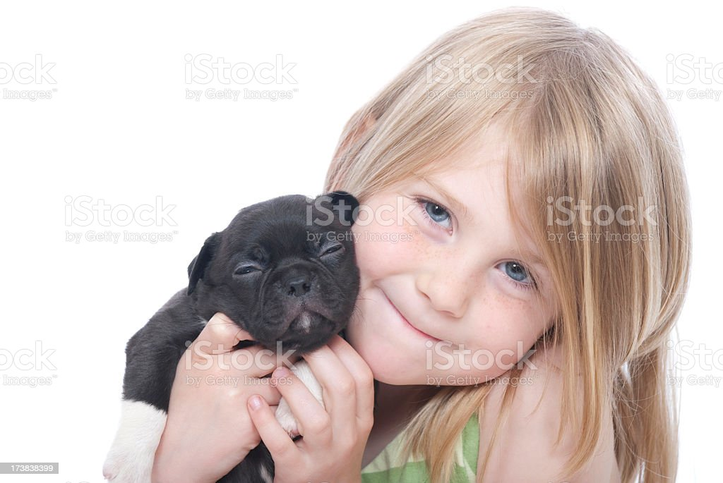 A little girl holding a black puppy on a white background royalty-free stock photo