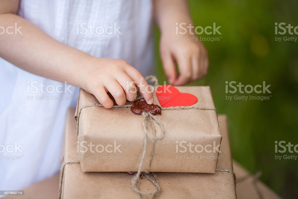 Little girl holding a gift box, Close-up. stock photo
