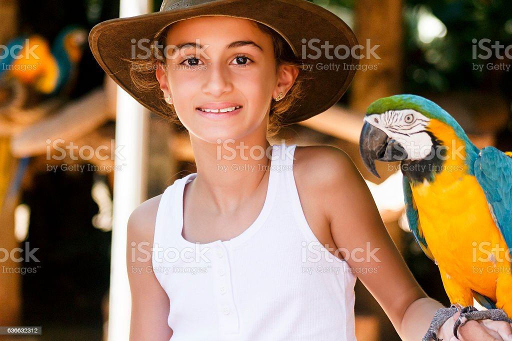 Little Girl Holding a Macaw in her Arm stock photo