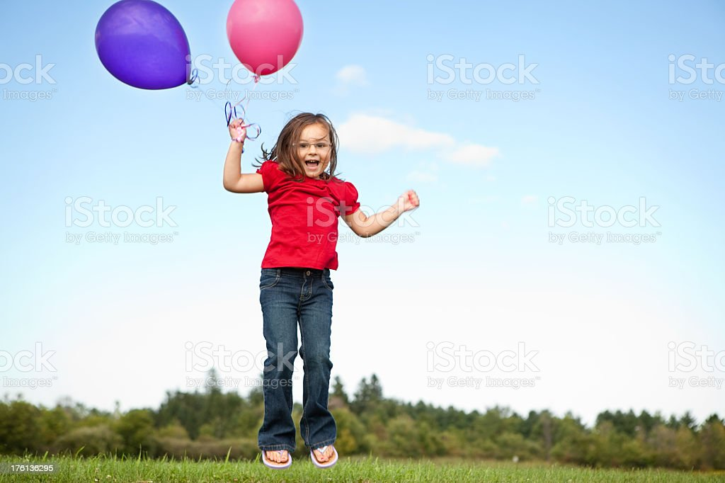 Little Girl Holding Balloons and Jumping Outside royalty-free stock photo