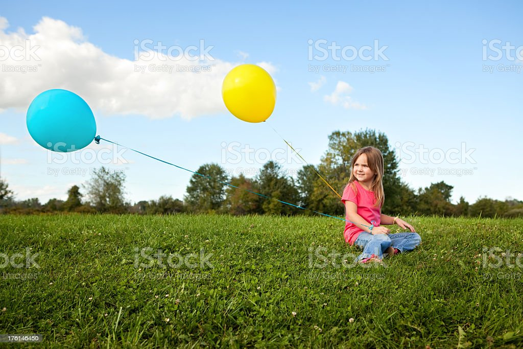 Little Girl Holding Balloons and Sitting in the Grass royalty-free stock photo