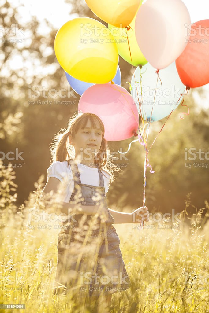 Little girl holding balloons outdoors royalty-free stock photo