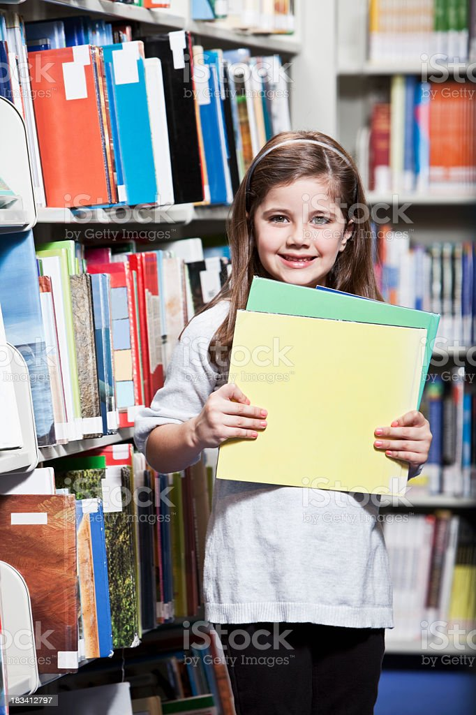 Little girl holding books in school library stock photo