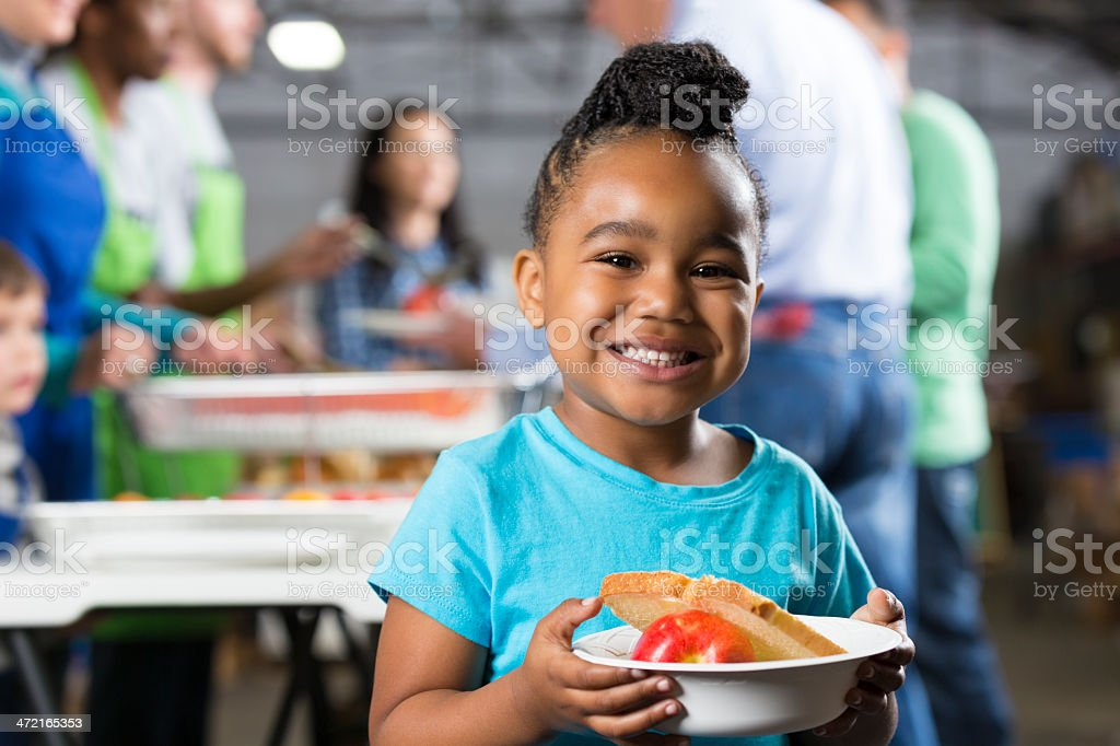 Little girl holding bowl at soup kitchen or food bank stock photo
