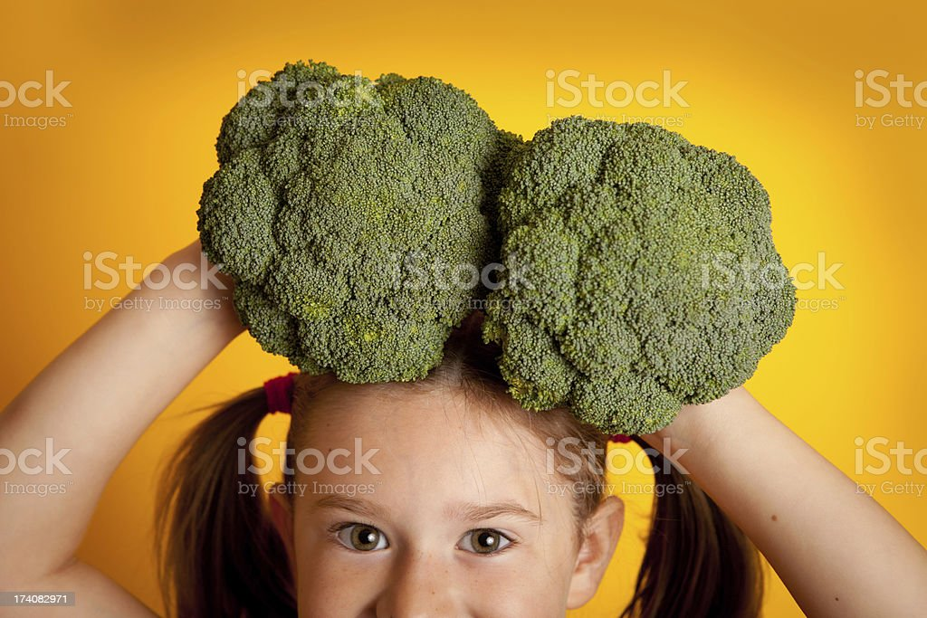 Little Girl Holding Broccoli On Her Head royalty-free stock photo