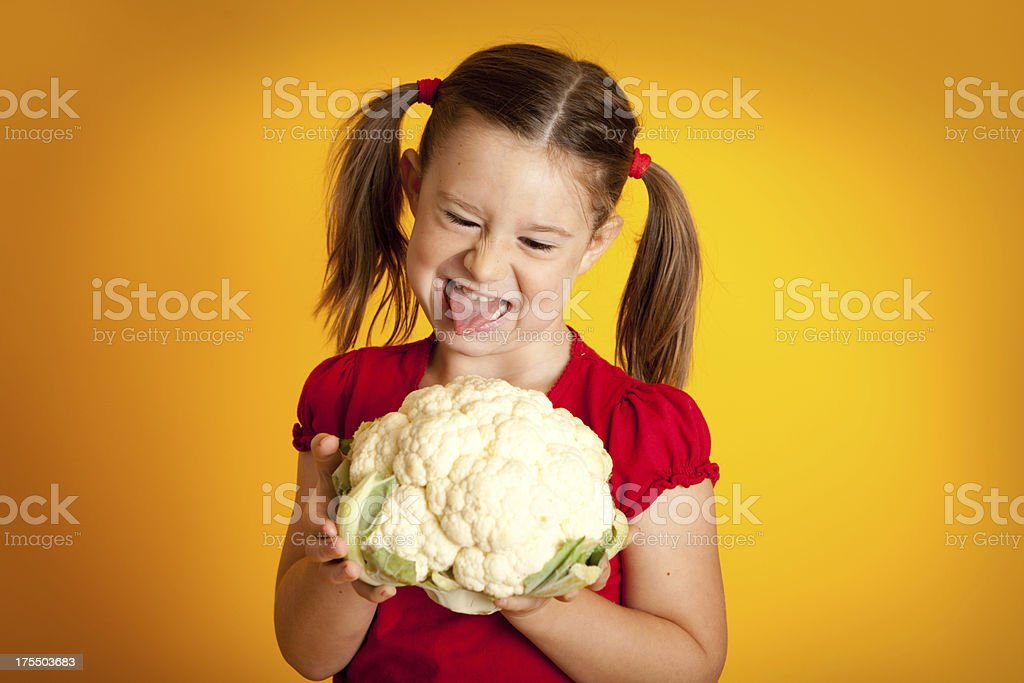 Little Girl Holding Cauliflower and Sticking Out Her Tongue royalty-free stock photo