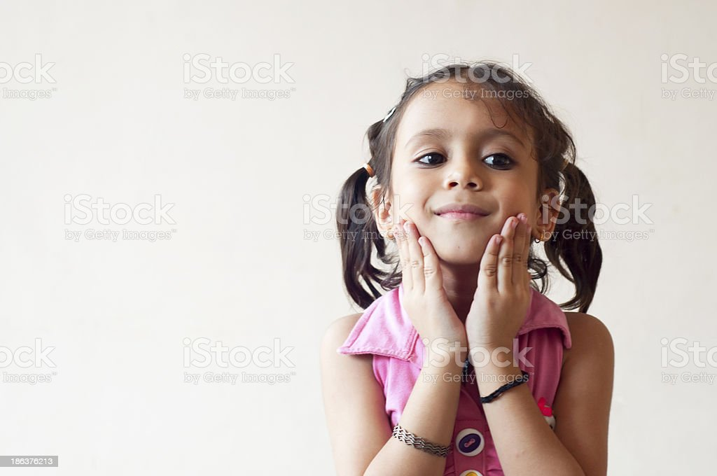 Little girl holding cheeks with her hands stock photo