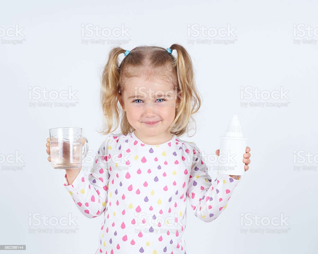 Little girl holding filter for drinking water and  glass stock photo