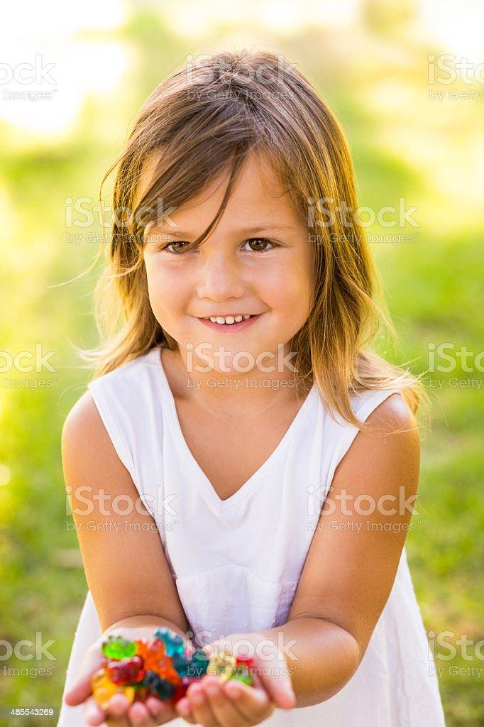 Little girl holding gummy bears stock photo