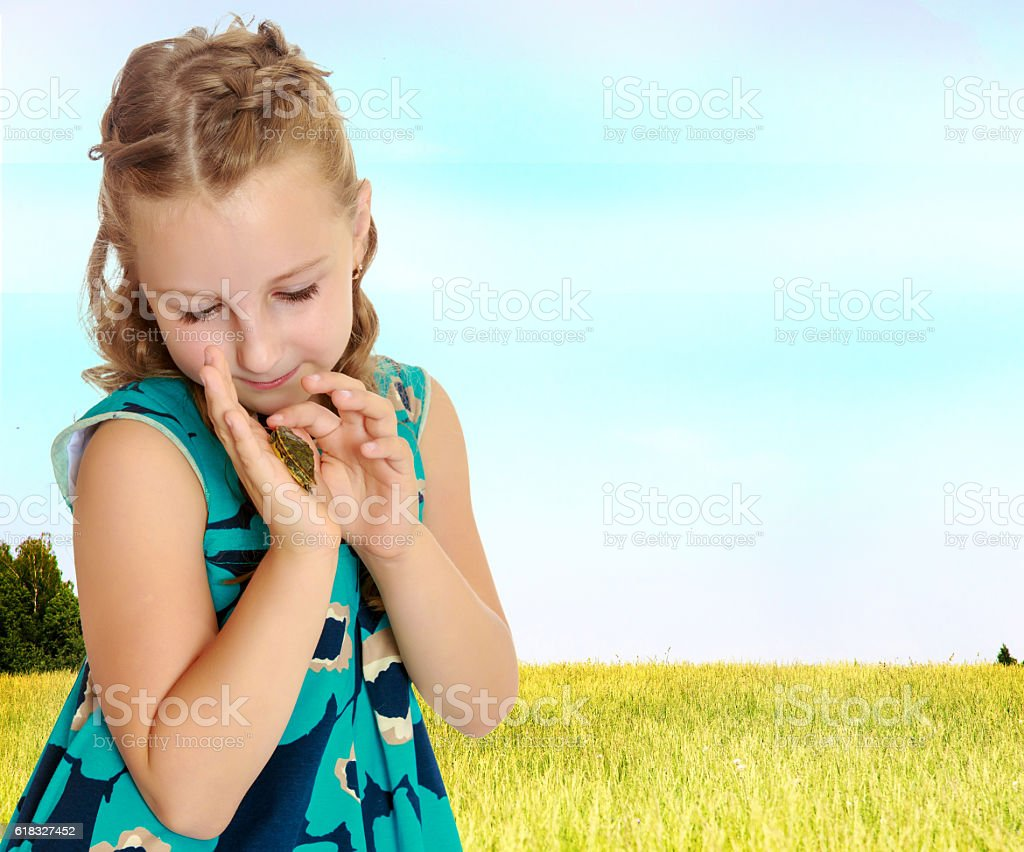 little girl holding in hands a small turtle. stock photo