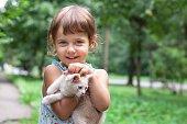 Little girl holding kitten. Outdoor