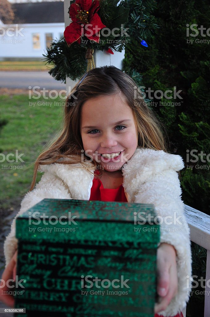 Little Girl Holding Out Christmas Gift Box stock photo