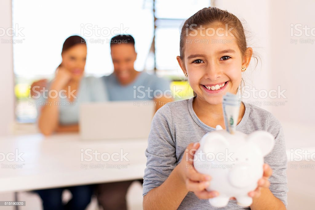 little girl holding piggybank stock photo