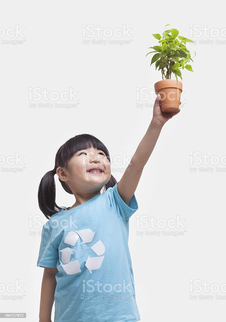 Little girl holding potted plant above her head, studio shot stock photo