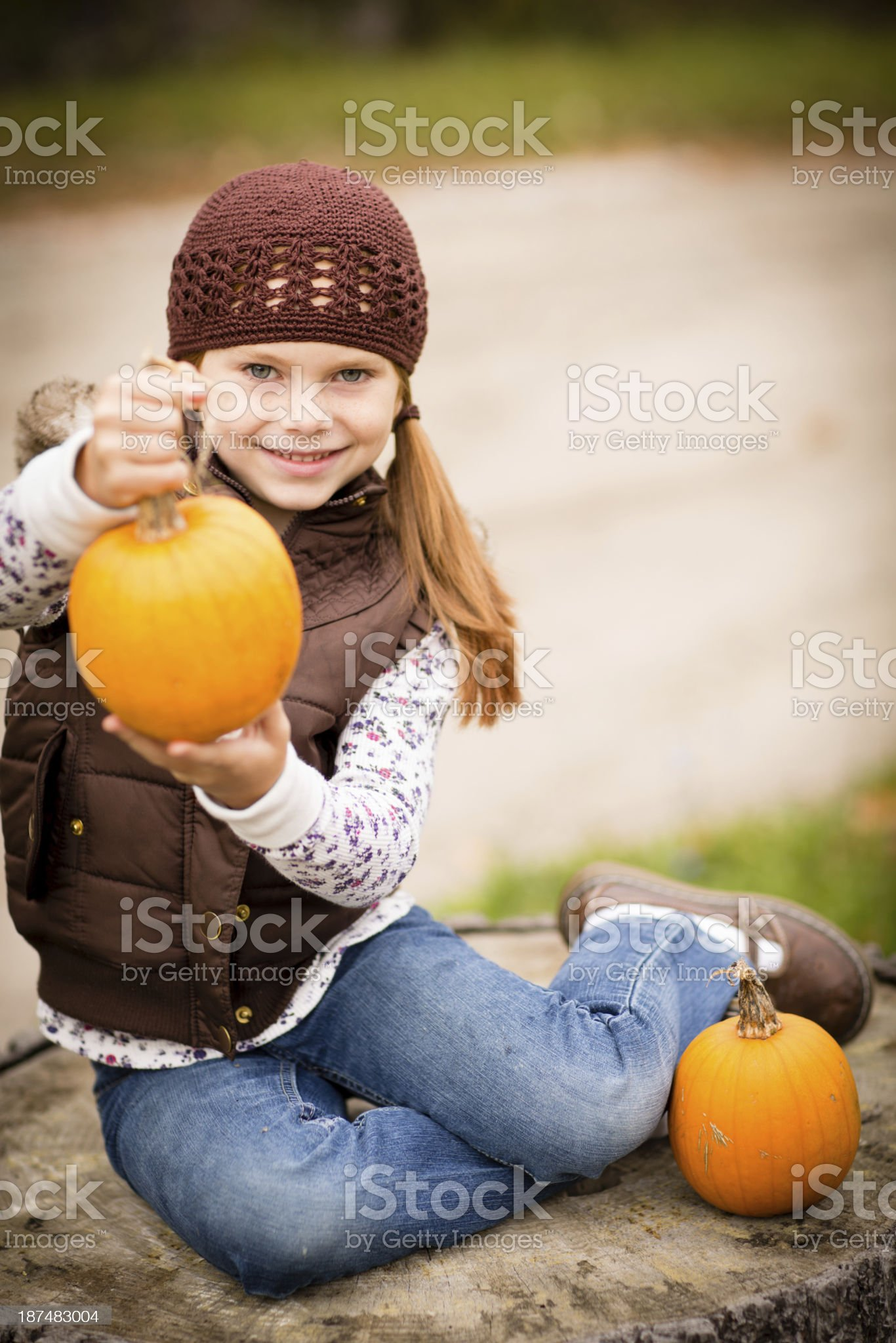 Little Girl Holding Pumpkin While Outside on Fall Day royalty-free stock photo