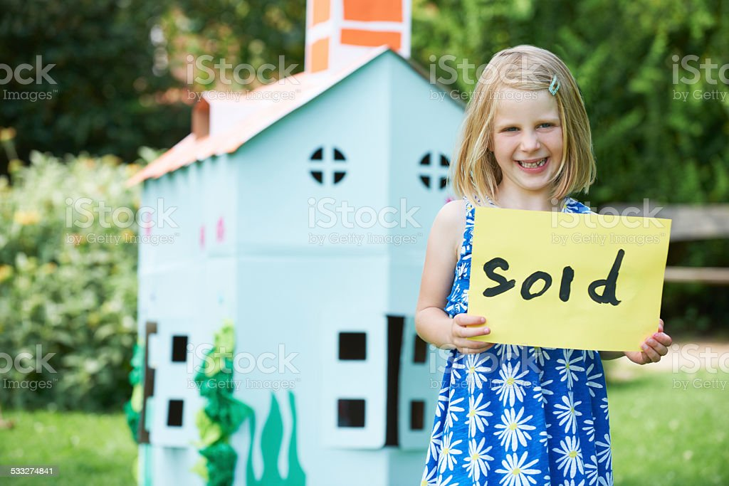 Little Girl Holding Sold Sign Outside Cardboard Playhouse stock photo
