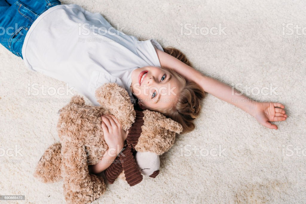 little girl holding teddy bear and looking at camera while lying on carpet at home stock photo