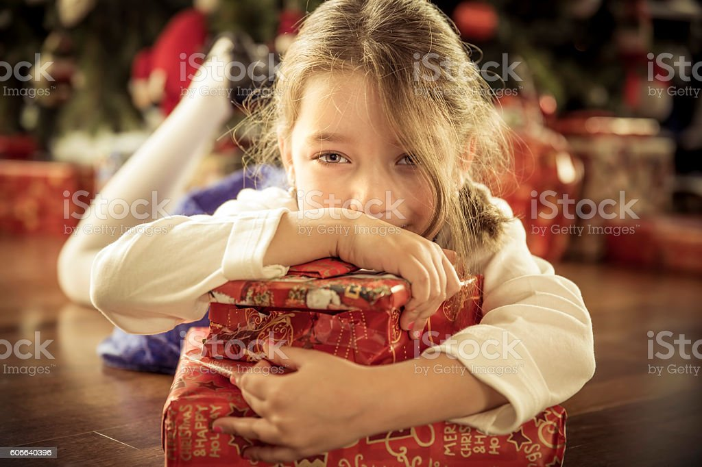 Little girl holding tight onto her Christmas gifts stock photo
