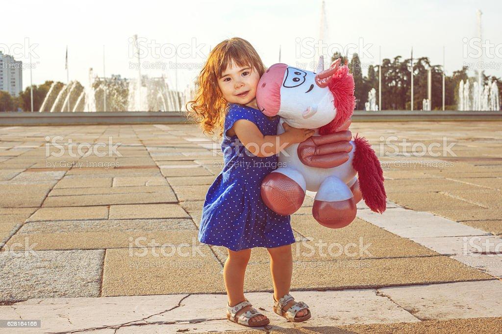 Little girl holding toy unicorn stock photo