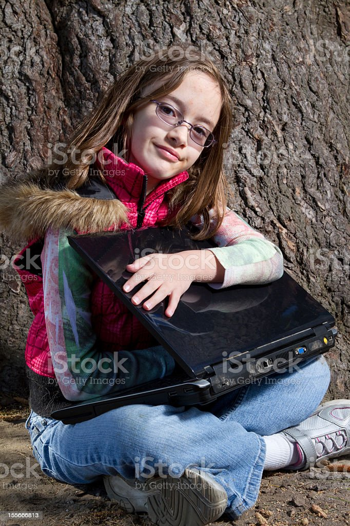 Little girl holds her laptop while sitting beside a tree. stock photo