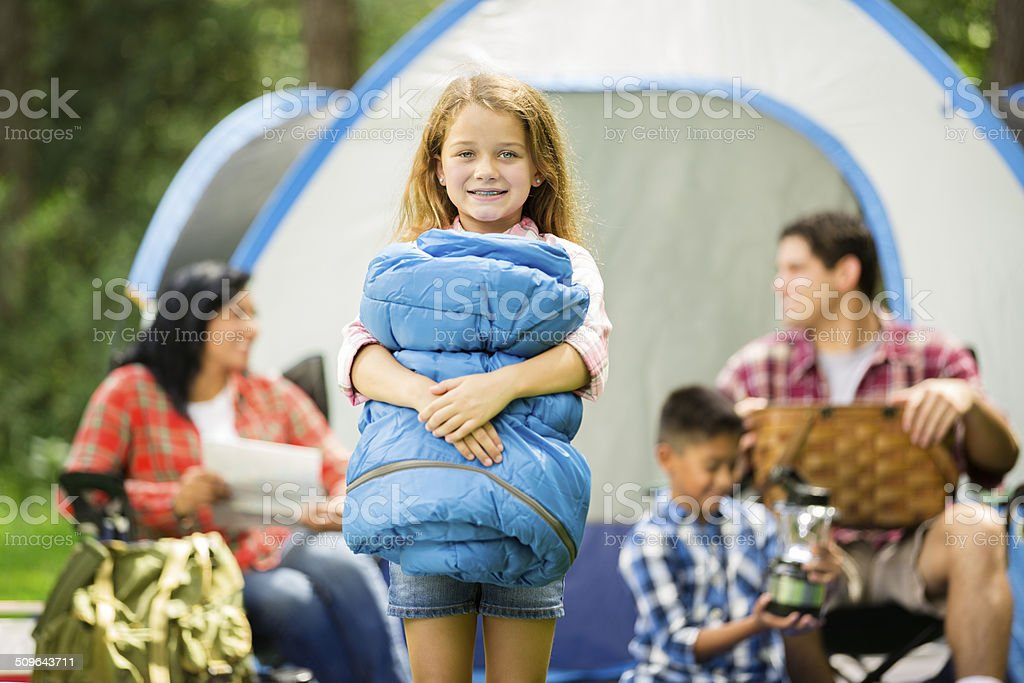 Little girl holds sleeping bag. Family camping outdoors in forest. stock photo