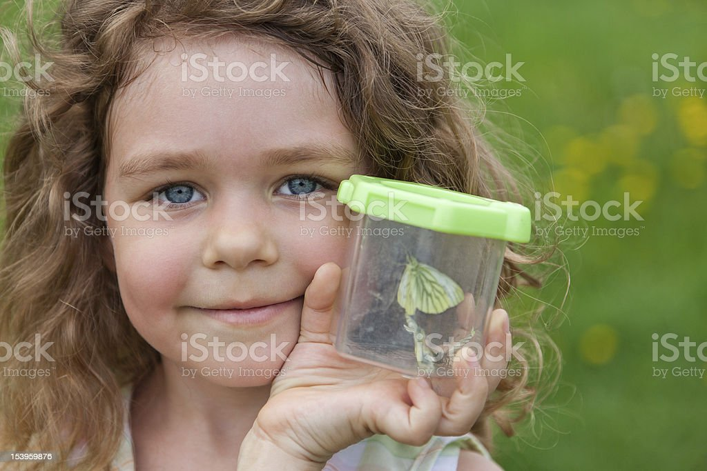 Little girl holds the container with caught butterfly stock photo