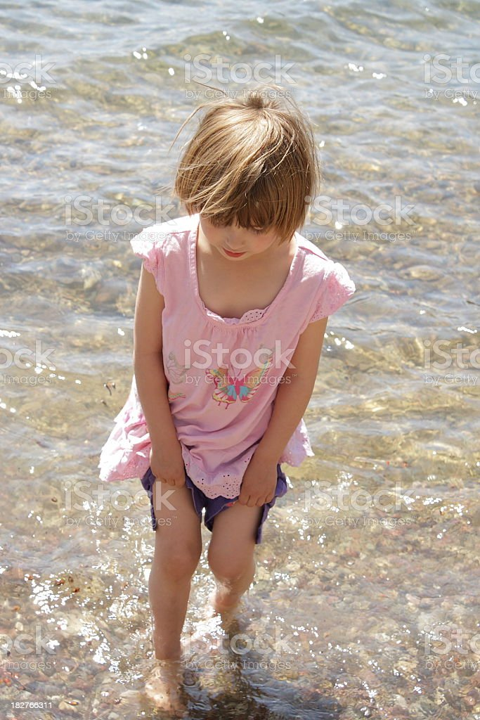 little girl holds up pants walking gingerly through lake water royalty-free stock photo