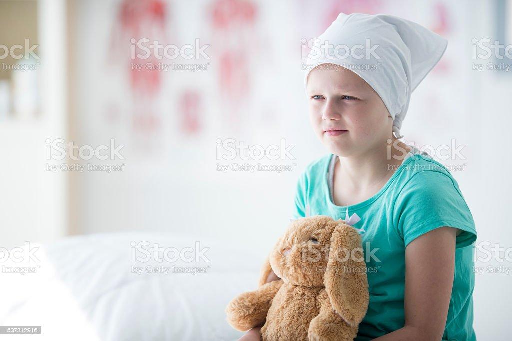 Little Girl Hopefully Sitting with Her Stuffed Animal stock photo