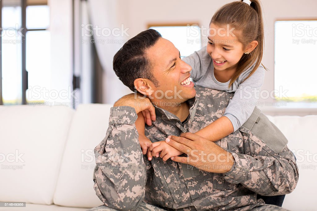 little girl hugging her military father stock photo