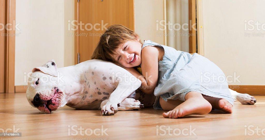 Little girl hugging white dog stock photo