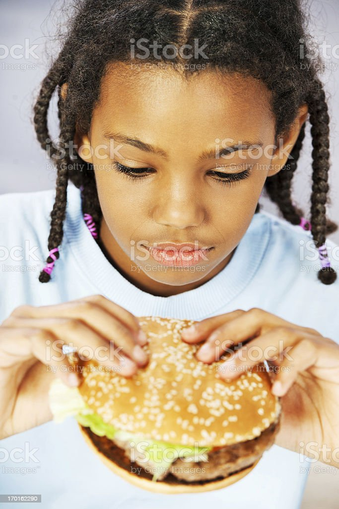 Little girl hungrily looking at hamburger. stock photo