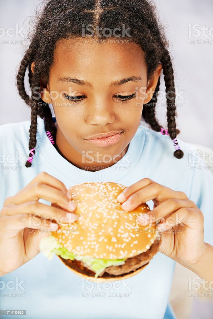 Little girl hungrily looking at hamburger stock photo