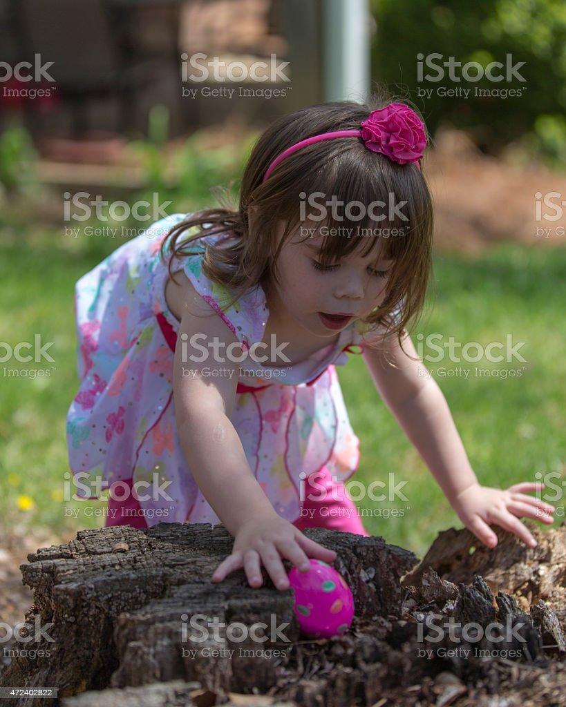 Little girl hunting Easter eggs stock photo
